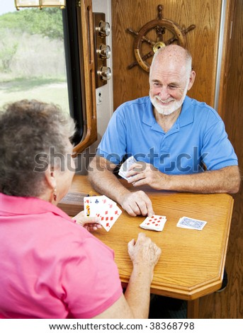 Retired senior couple playing a game of cribbage in the kitchen of their motor home.