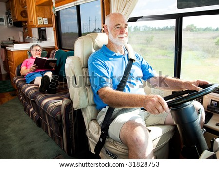 Retired senior couple traveling by motor home.  The husband drives while the wife reads in back.