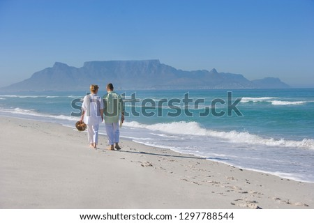 Retired senior couple walking away from camera on beach vacation