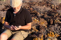 Retired senior man with cap and a black polo shirt while using cellphone. Sitted outdoor in arid tropical area with volcanic rocks.