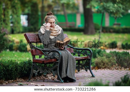 592c4804d3944 Retired woman reading a book on the bench  733221286