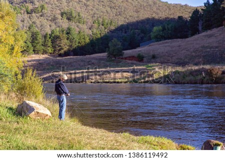 Retiree fly fishing in a fast flowing river for trout