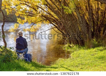 Retiree sitting on a chair fly fishing for trout on the Murray River New South Wales Australia