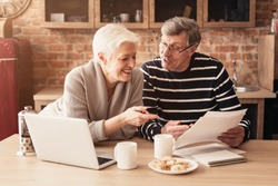 Retirement Financial Planning Concept. Happy Senior Couple Discussing Family Budget Together, Sitting In Kitchen With Laptop And Papers