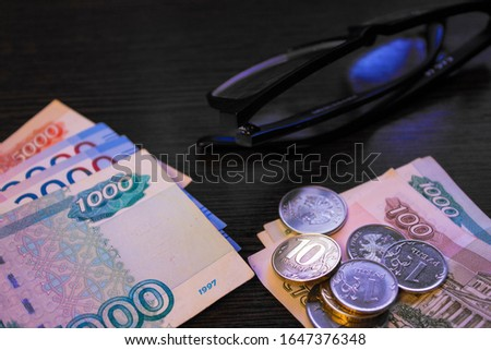 Retirement pension in Russian money. Banknotes and coins on a table close up on a black background. Indexation and benefit allowance in Russia.