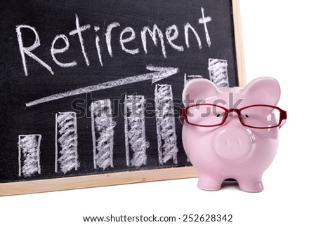 Retirement plan : Pink piggy bank with glasses standing next to a blackboard with retirement savings message.  Investment, growth, retire concept.
