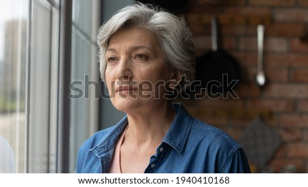 Retirement problems. Worried depressed old age latin lady stand by window look away troubled with bad health loneliness. Upset mature hispanic grandma miss children husband lost in sad heavy thoughts
