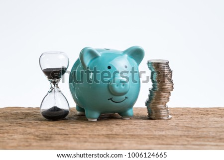 Retirement saving money piggy bank as long term investment concept with stack of coins and sandglass or hourglass on wood table and white background.
