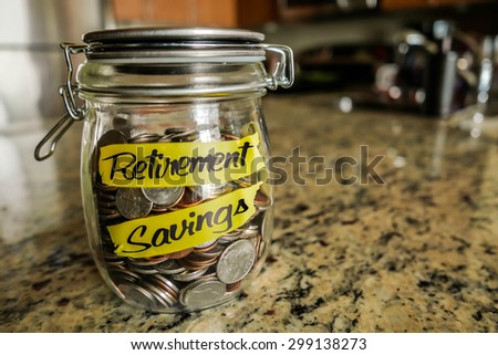 Retirement Savings Money Jar. A clear glass jar filed with coins and bills, saving money. The words