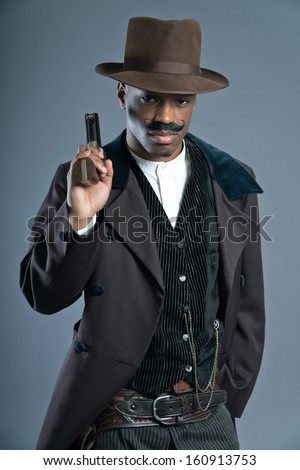 Retro Afro america western cowboy man with mustache. Ready to shoot. Wearing brown hat. Cool tough guy.