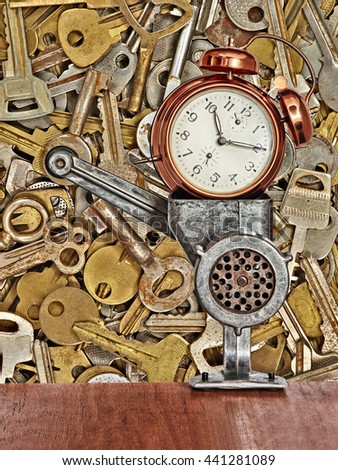 Retro alarm clock in meat grinder on old metal keys background taken closeup. #441281089