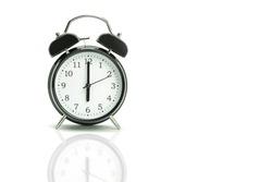Retro alarm clock on a white background. Black alarm clock showing 6 hours 00 minutes on a white background with copy space