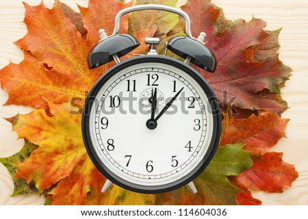 Retro alarm clock on autumn leaves. Time change concept. In autumn we change clock one hour back. Ageing, getting old and running out of time concept.