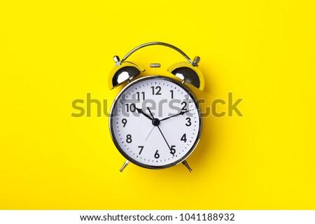 Retro alarm clock on bright yellow background #1041188932