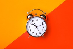 Retro alarm clock on half orange and red background