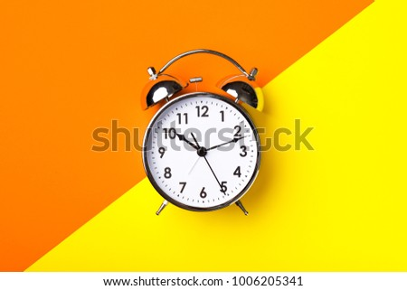 Retro alarm clock on half orange and yellow background #1006205341