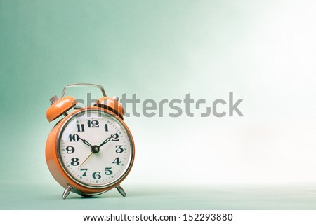 Retro alarm clock on table on mint green background