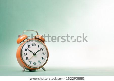 Retro alarm clock on table on mint green background