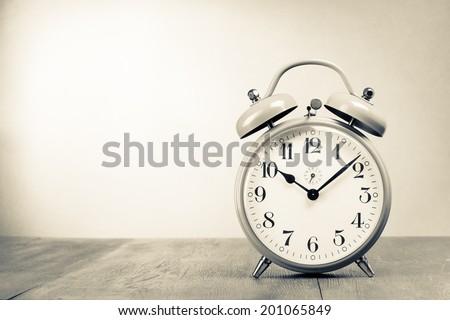 Retro alarm clock on table. Vintage style sepia photo