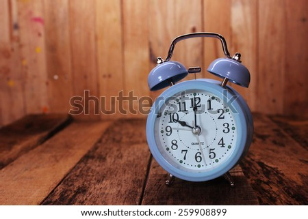 Retro alarm clock on the old wood background #259908899