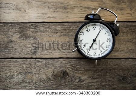 Retro alarm clock on wooden table #348300200