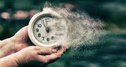 Retro alarm clock or vintage alarm clock in old hand. Time is running out concept shows clock that is dissolving away into little particles