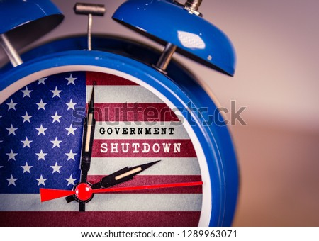 Retro alarm Clock with Government Shutdown text,and American Flag. USA shutdown, government closed and American federal shut down due to spending bill disagreement between the left and the right