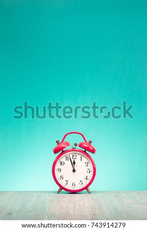 Retro alarm clock with last minutes to twelve o'clock on wooden table front gradient mint green wall background. Vintage old style filtered photo