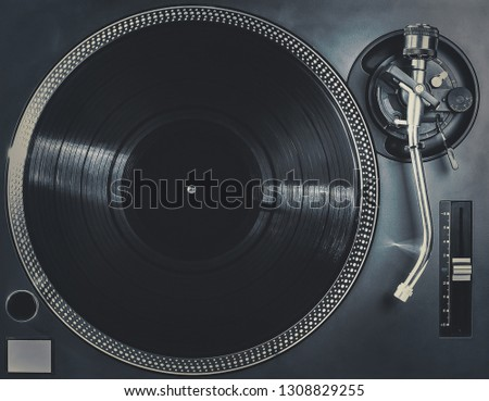 Retro analog dj turntable overhead shot.Professional disc jockey music player turn table top view.High quality vintage audio equipment for hip hop concert in night club.Play music in hifi