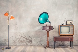 Retro analog television on wooden TV stand with outdated amplifier, old radio receiver from 60s, classic gramophone, floor lamp front aged concrete wall background. Vintage style filtered photo