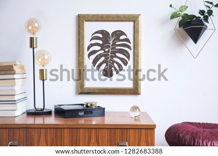 Retro and minimalistic interior with gold mock up poster frame on the vintage brown shelf, hanging plant in design pot, books, platns, table lamp and box.  #1282683388