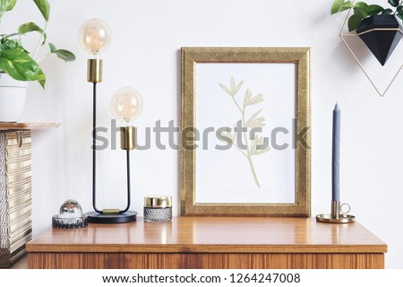 Retro and minimalistic interior with mock up photo frame on the vintage brown shelf, hanging plant in black pot, table lamp, gold organizer and plants. #1264247008
