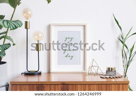 Retro and minimalistic white interior with mock up photo frame on the vintage brown shelf,tropical plant in cement pot, table lamp, gold pyramid and accessories. #1264246999