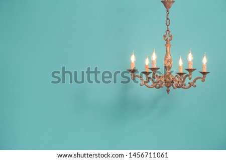 Retro antique old bronze chandelier with bulb lamps shaped candles hanging front mint blue wall background. Nostalgia lighting concept. Vintage style filtered photo #1456711061