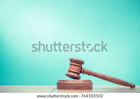 Retro auction or judge wooden gavel on table front mint green background. Vintage old style filtered photo
