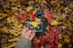 retro audio cassette in hand, autumn natural background. atmosphere image of autumn music. inspiration, melody, nostalgia concept. fall season