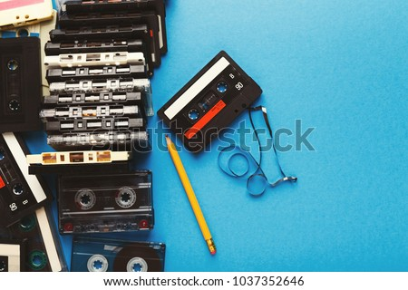 Retro audio cassettes and pencil on blue background. Top view on vintage tapes and simple device for rewinding, copy space. Obsolete technology concept #1037352646