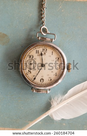Retro background, old watches on a blue background and feather,  vintage.The Victorian era. Writer, literature, old school, polite learning concept.