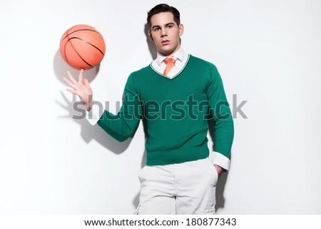 Retro basketball fashion man wearing a green sweater orange tie and white shorts. Studio shot against white wall.