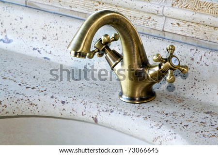 Retro bathroom faucet on marble water basin