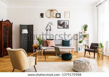 Retro beige armchair and pouf on the cozy carpet in contemporary living room interior with grey sofa and vintage furniture #1379170988