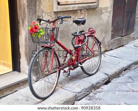 Retro bike in red with a bouquet of flowers in the basket