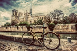 Retro bike next to Notre Dame Cathedral in Paris, France and the Seine river. Vintage