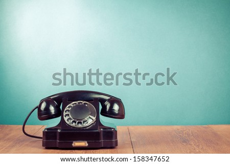 Retro black telephone on table in front mint green background #158347652