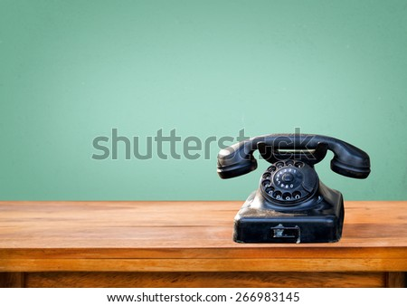 Retro black telephone on wood table with vintage green eye light wall background #266983145