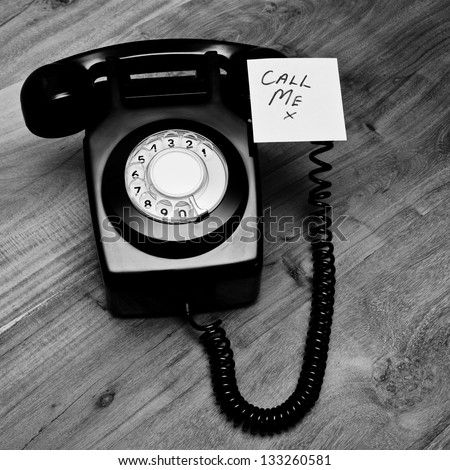 Retro black telephone with reminder note to call