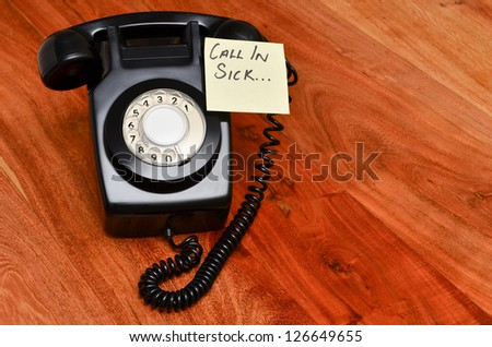 Retro black telephone with reminder note to call in sick