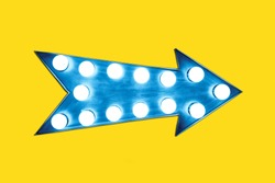 Retro blue arrow shaped vintage colorful illuminated metallic display sign with glowing light bulbs on a empty vivid yellow background.