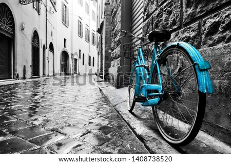 Retro blue bike on old town street. Color against black and white. Vintage style. Florence, Italy #1408738520