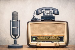 Retro broadcast table radio receiver with green eye light, studio microphone circa 1950 and telephone front concrete wall background. Listen music concept. Vintage instagram old style filtered photo